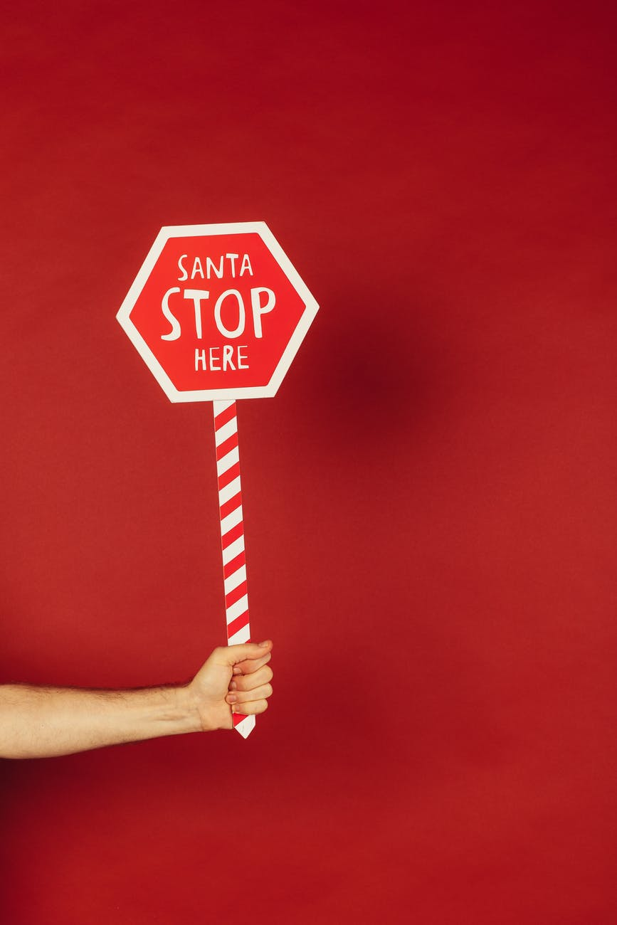 person holding red and white santa stop here sign