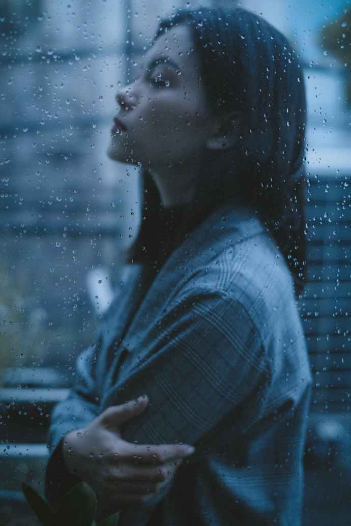 unhappy thoughtful teen girl arms crossed in rainy day